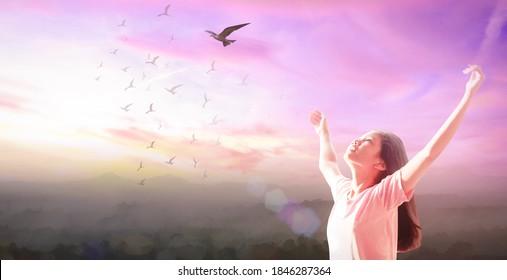 Freiheitskonzept: Schönes Mädchen auf dem Himmel und Vögel fliegen Sonnenuntergang