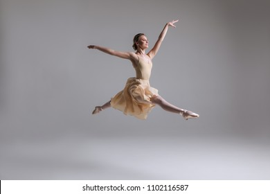 Release your soul! Gorgeous good-looking attractive young tender modern ballet dancer performing art jump with empty copy space background.