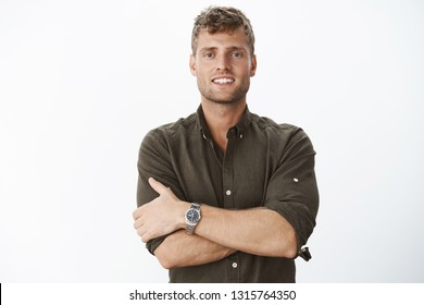 Reliable and confident boyfriend on guard. Charming blond man with blue eyes and bristle cross hands around body and smiling cheeky standing in self-assured assertive pose against gray background