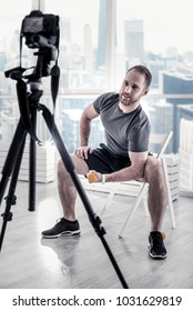 Relief biceps. Appealing energetic male blogger posing on chair while training near window and rising dumbbell
