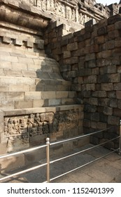 "Relief carving on the lower part of Borobudur Temple showing stories related to ""Kamadhatu"", the lowest level of human lust, now protected with fence."