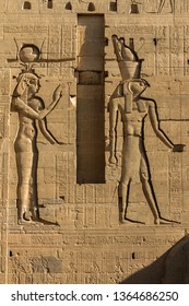 Relief Carvings of Hathor and Osiris on the First Pylon of the Temple of Isis at Philea, Aswan Egypt. The pylon is covered with hieroglyphs and relief carvings from the Ptolemaic Period of the kingdom