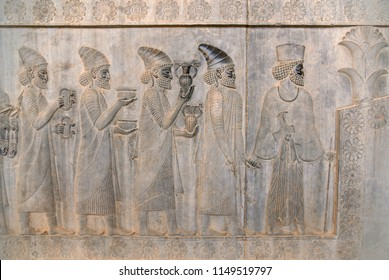 The relief depicts ambassadors, bearing gifts to the king. Ancient relief on the wall of the ruined city of Persepolis. Persepolis. Iran.