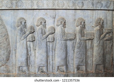 The relief depicts ambassadors, bearing gifts to the king. Ancient relief on the wall of the ruined city of Persepolis. Persepolis. Iran.one of world heritage site ,UNESCO