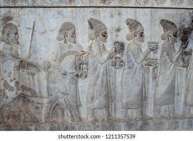 The relief depicts ambassadors, bearing gifts to the king. Ancient relief on the wall of the ruined city of Persepolis. Persepolis. Iran. one of world heritage site ,UNESCO