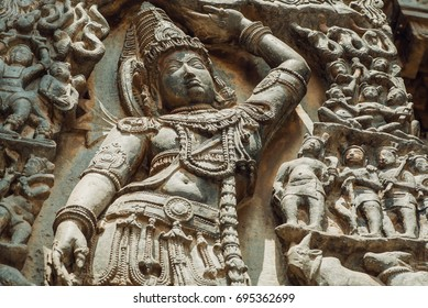 Relief with Lord Krishna lifting Mt. Govardhan. Artwork of the 12th century stone ornate Hoysaleshwara temple in Halebidu, India.