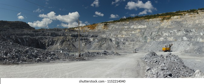 Relief of the quarry for limestone mining against the background of a blue sky with clouds, panorama. Mining industry.
