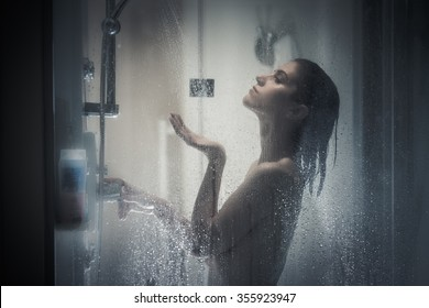 Relief and relaxation after long stressful day.Taking moment for yourself concept.Skincare,spa and aromatherapy.Unfocused portrait of a woman showering through the bath screen with little drops