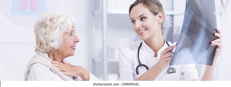 Relieved elderly woman talking to her smiling doctor who is holding an X-ray