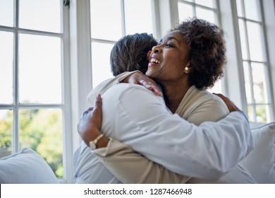 Geliebte reife Frau, die ihren Hausarzt umarmt.