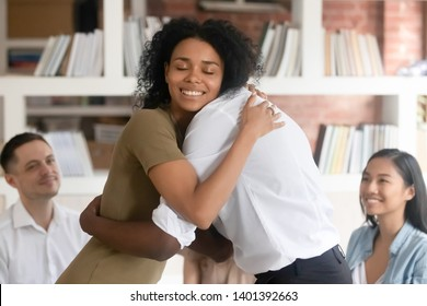 Relieved smiling black woman hug with friend showing support and empathy at group therapy session, diverse people embrace help overcome psychological problems or addiction at counselling or treatment