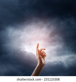 religion concept. finger touching the magic sky
