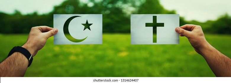 Religion conflicts as global issue concept. Two hands holding different faith symbols, Islam vs Christianity belief over green field nature. Relations between different people doctrines and church.