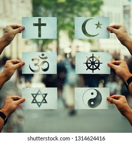 Religion conflicts as global issue concept. Human hands holding different paper with faith symbols over crowded street scene. Relations between different people doctrines and beliefs, social problem.