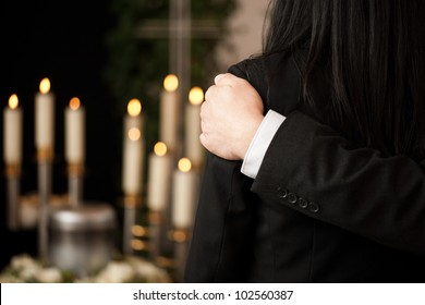 Religion, death and dolor  - couple at funeral consoling each other in view of the loss