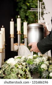 Religion, death and dolor  - mortician on funeral with urn