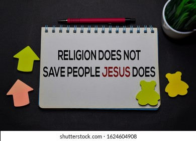 Religion Does Not Save People Jesus Does write on a book isolated on office desk. Christian faith concept