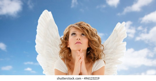 religion, faith, holidays and people concept - praying teenage girl or young woman with angel wings over blue sky and clouds background