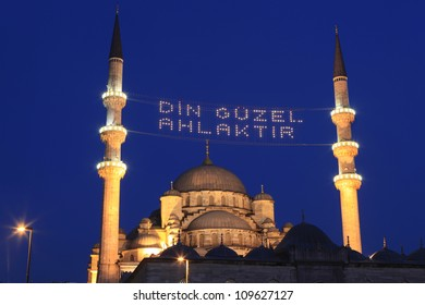 """Religion is good morals"" lettering hanging on New Mosque's mahya in Istanbul,Turkey. Mahya is an enlightenment arrangement during ramadan nights between two minarets."
