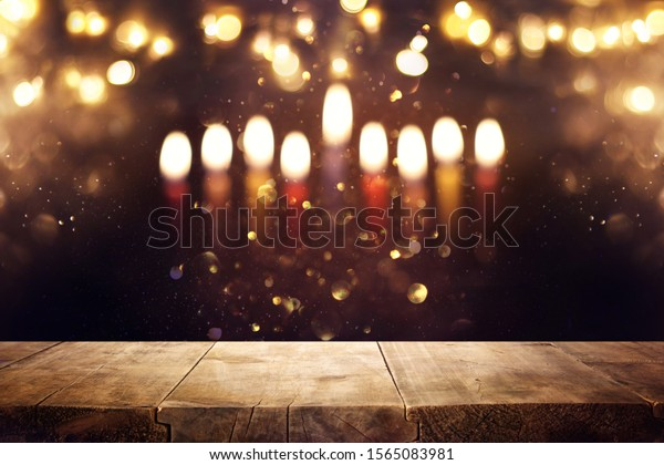 religion image of empty wooden table in front of jewish holiday Hanukkah background with menorah (traditional candelabra). For product display