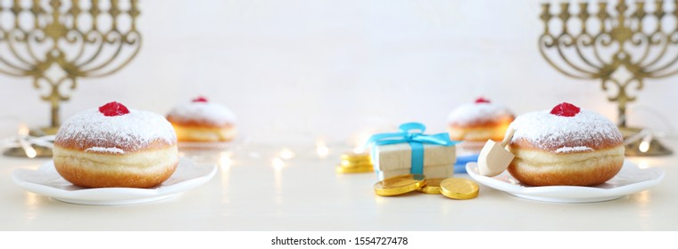 religion image of jewish holiday Hanukkah with spinning top and doughnut over white background