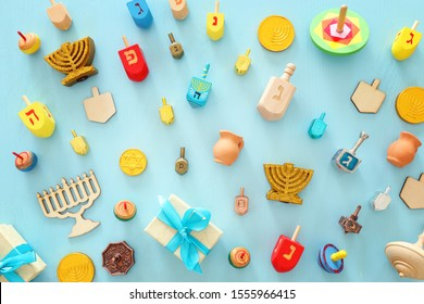 religion image of jewish holiday Hanukkah with menorah (traditional candelabra), spinning top over wooden blue background. top view, flat lay