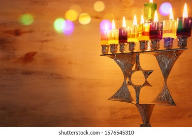 Religion image of jewish holiday Hanukkah background with david star menorah (traditional candelabra) and colorful oil candles