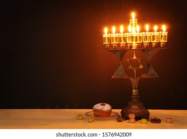 Religion image of jewish holiday Hanukkah background with bronze david star menorah (traditional candelabra) and oil candles