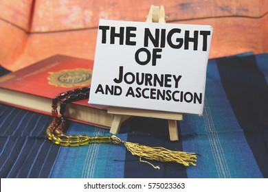A religion Islamic concept of a Prayer beads tasbih on a holy Quran over a blue pattern design background with a wooden tripod and white canvas with a word THE NIGHT OF JOURNEY AND ASCENSION