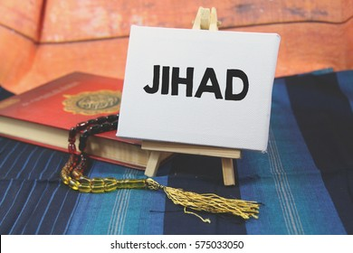 A religion Islamic concept of a Prayer beads tasbih on a holy Quran over a blue pattern design background with a wooden tripod and white canvas with a word JIHAD