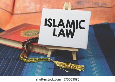 A religion Islamic concept of a Prayer beads tasbih on a holy Quran over a blue pattern design background with a wooden tripod and white canvas with a word ISLAMIC LAW