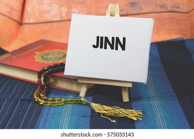 A religion Islamic concept of a Prayer beads tasbih on a holy Quran over a blue pattern design background with a wooden tripod and white canvas with a word JINN