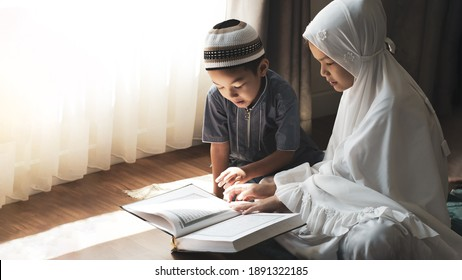 Religious Asian Muslim kids learn  the Quran and study Islam after pray to God at home .Sunset light shining through the window.Peaceful and Marvelous warm climate.  - Shutterstock ID 1891322185