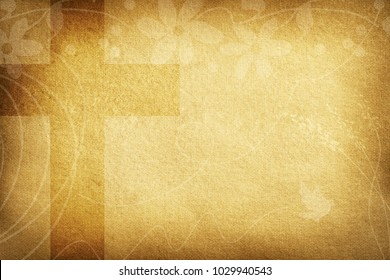 Religious card with brown textured fabric background decorated with flowers and big cross.
