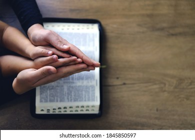 Religious Christian girl praying with her mother indoors. Bible in background. Space for text