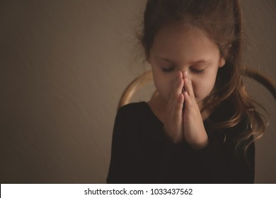 Religious Christian girl praying on color background