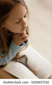 Religious Christian girl praying over Bible indoors