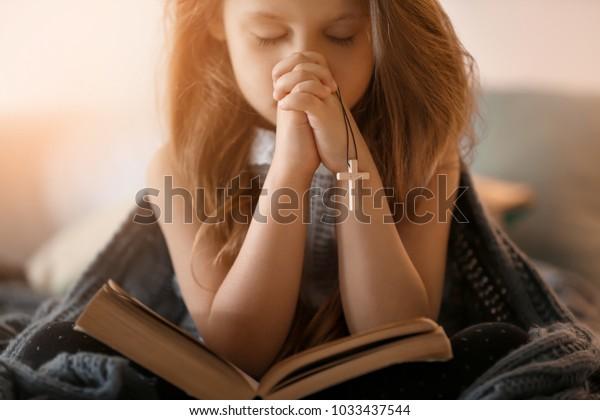 Religieuse chrétienne priant sur la Bible à l'intérieur