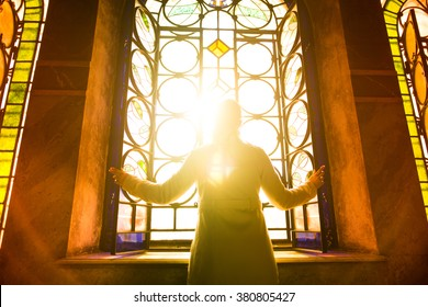 Religious christian woman looking trough the stained glass church window light.Woman praying to god at St. Alexander Nevsky Cathedral.Christianity.Strong religion,faith and hope concept.Enlightenment
