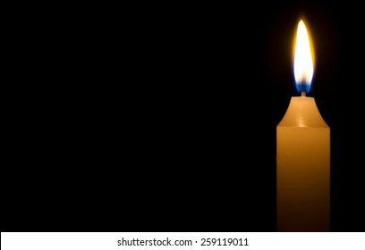 Religious concept. Burning candle on dark background