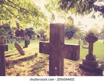 Croix religieuse au cimetière. Scène lumineuse d'un vieux cimetière européen avec une pierre tombale en forme de croix à l'avant. Des sentiments positifs et pacifiques.