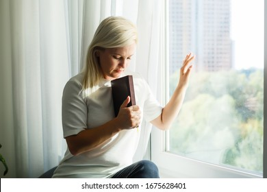 Religious faithful middle aged woman praying with hope faith holding hands clasped together in namaste at home in morning, old mature lady believer christian saying worship prayer with eyes closed