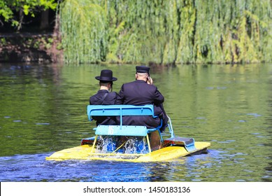 Religious Jew. 2 Hasidic Jews in traditional black clothes ride an old catamaran on the lake in the  Park in Uman, Ukraine. Time of the Jewish New Year