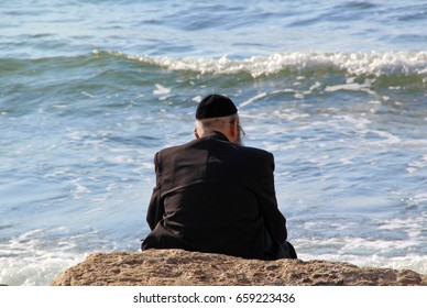 Religious Jew sitting on the coast of Mediterranean sea in Israel and watching the waves, deep in thought.