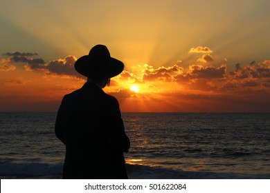 Religious Jew standing on the coast of Mediterranean sea in Israel and watching the sunset, deep in thought.