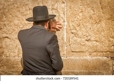 Religious Jewish man seen from the back, Orthodox Jew praying at the Western wall (Wailing wall), Jewish prayer. Orthodox Judaism, Jewish holidays stock image.