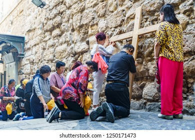 Religious korean tourists praying in via dolorosa ( way of sorrow, believed to be the path that Jesus walked on the way to his crucifixion ) in jerusalem in israel ( palestine ) 24 october 2018