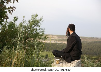 Religious man sits alone in solitude meditating in spiritual connection to God
