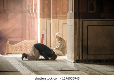 Religious muslim man praying inside the mosque. Two older Muslims at the great Friday Mosque Jami Masjid in New Delhi, India. 8 January 2018