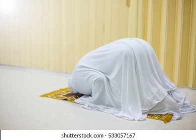 Religious muslim woman praying inside the mosque.